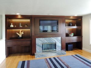Mahogany niche inset cabinets with LED illumination and framed in TV. fireplace surround with granite fireplace